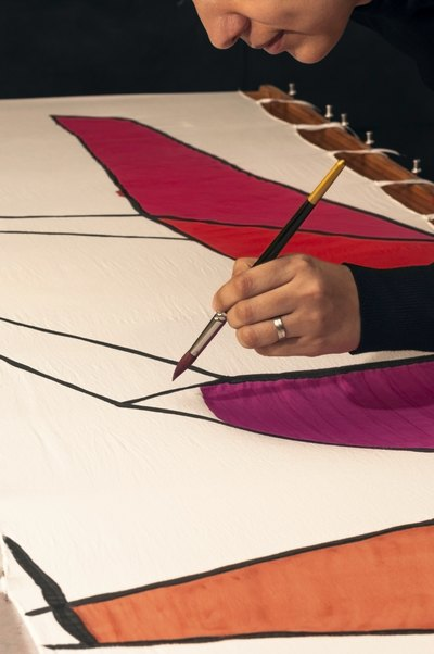 Close-up of a woman's hand painting a cloth banner