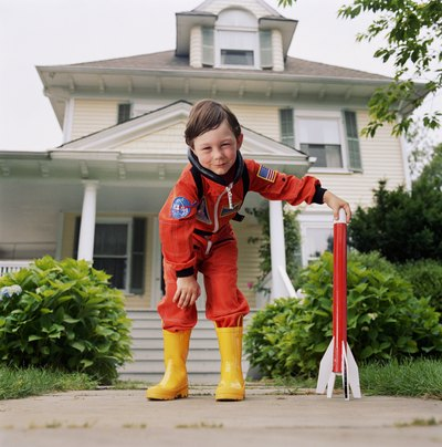 Boy in astronaut outfit holding rocket