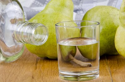 Fruit brandy in a glass with pears in the background.