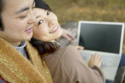 A man embraces a woman while she is looking at a computer.
