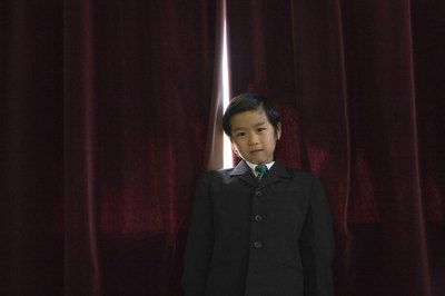 A boy wearing a suit in front of red curtains.