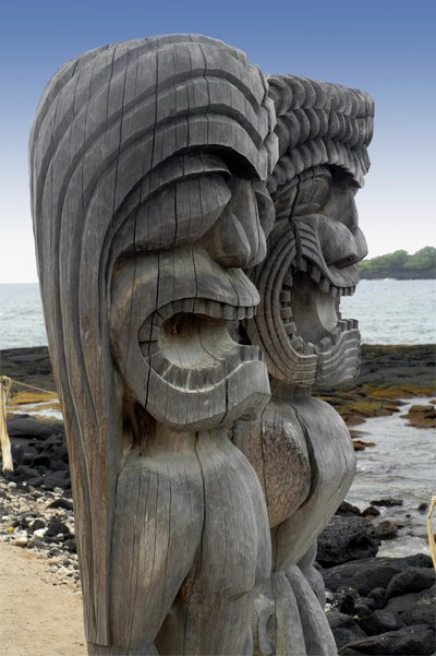Two Tiki gods on an island beach.