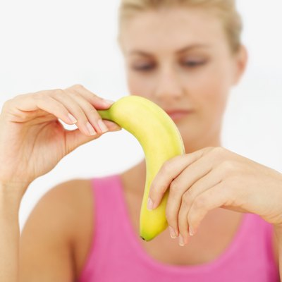 A woman is peeling a banana.