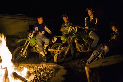 Friends on dirt bikes around camp fire