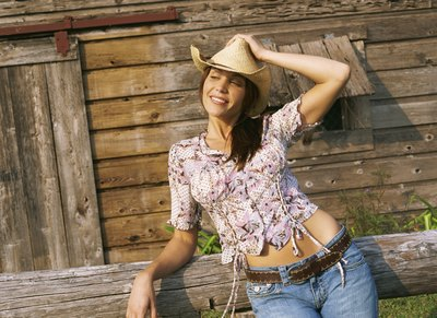 Young woman wearing cowboy hat on farm