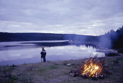 a couple standing on the shore with a campfire in the foreground.