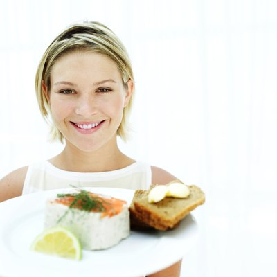 Woman serving smoked salmon on tray