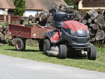 A garden tractor parked in front of a woodpile