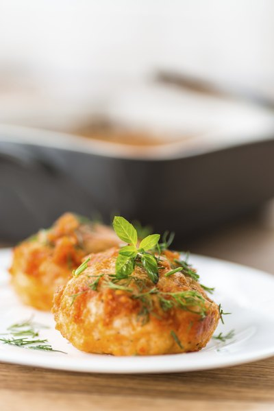 A close-up of meatballs on a dish garnished with fresh herbs.