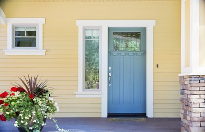 A view from the porch of a Craftsman cottage painted yellow with white trim and blue accents.