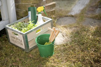 Gardening supplies in a wooden crate outdoors.
