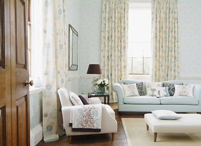Curtains gracing ceiling to floor windows in a traditional living room decorated with soft patterns and hues.