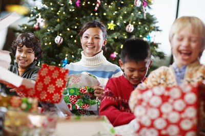 Four happy children open gifts by a decorated tree.
