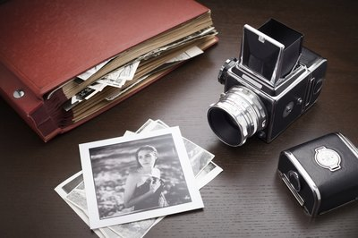 Vintage photos and a scrapbook on a desk.