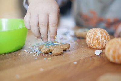 A close-up of a child adding sprinkles to a gingerbread cookie.