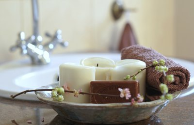 A close-up of a bowl filled with candles, soap, a rolled washcloth, and a sprig of flowering vine.