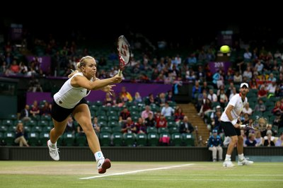 Players compete in doubles on the grass courts at Wimbledon.