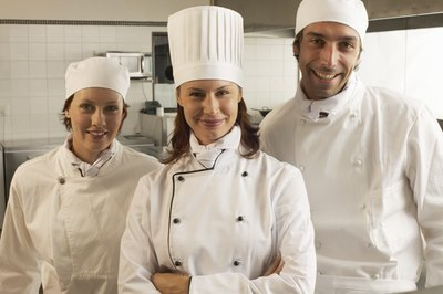 Chefs' toques are customarily worn, not part of a required kitchen employee uniform.