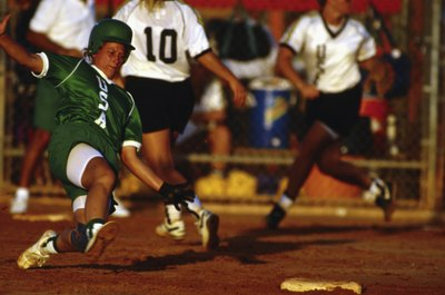 A softball player wearing a helmet slides into the base.