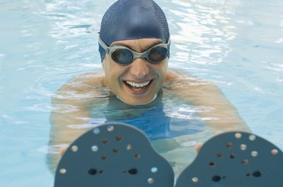 Use swimming paddles to move your upper-body muscle building to the water.