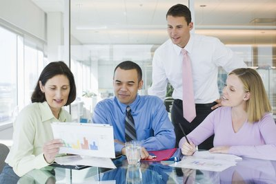 Business analysts meet with customers to review documents.