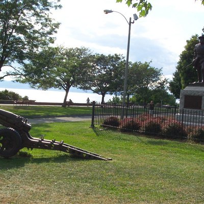 Battery Park In Burlington. Located At The Top Of Battery Street In Downtown Burlington, Lies Battery Park. This Historic Park, Deeded To The City In 1870, Boasts A Panoramic View Of Lake Champlain And The Adirondacks, With A Promenade, Playground, Monuments And A Bandshell. A Commemorative Cannon And A Statue Of Vermont'S Famous Civil War General William W. Wells Is Captured In This Photograph.The Cannon Is A 75 Mm Pack Howitzer, M116 Or Similar.