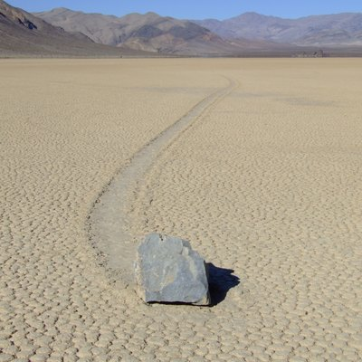 Landscape image; Location: Racetrack Playa in Death Valley National Park; view is south-to-north from near the southern edge of the playa. The Grandstand is visible on the horizon a little to the right of the center of the image. Note the track through the dried mud behind the boulder. These tracks are left when winter storms dampen the surface of the playa, which consists of extremely fine grained clay that becomes very slippery when wet, and also produce wind speeds high enough to break the rock loose and push it along. The rocks originate in the mountains surrounding the racetrack, and there are several hundred scattered around the playa. The average size of the rocks that leave these tracks is 50kg.