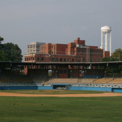 Durham Athletic Park in Durham, North Carolina. In the background are the headquarters of Measurement Incorporated and the North Carolina Mutual Life Insurance Company Building.