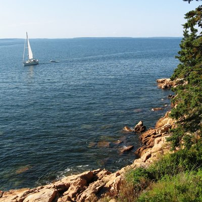 A Beach In Maine On A Clear Day With A Sailboat