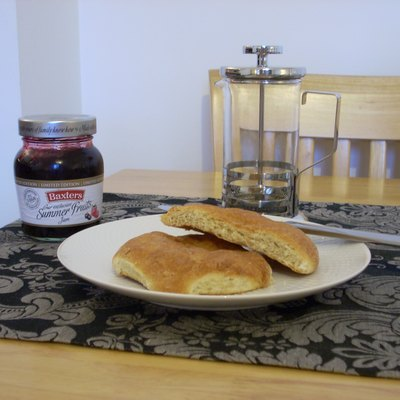Two Aberdeen butteries (also known as rowies) served with fruit preserve/jam, one cut in half to show interior. The Aberdeen buttery is a specialty of the city of Aberdeen, Scotland. It was originally eaten at sea by fishermen from the city, as an energy-dense food that was tastier than dry biscuits but would not go stale easily.