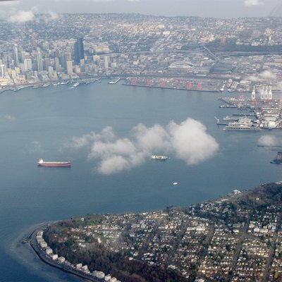 Aerial view of Elliot Bay in Seattle, facing east. Downtown in upper left. Alki point at bottom. Harbor Island in right center.
