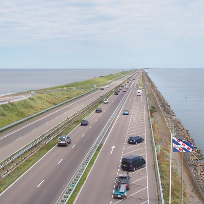 The Afsluitdijk looking north-eastwards towards Friesland from the monument tower. The Wadden Sea is to the left and the IJsselmeer is to the right. The Province Fryslân flag is in the foreground.