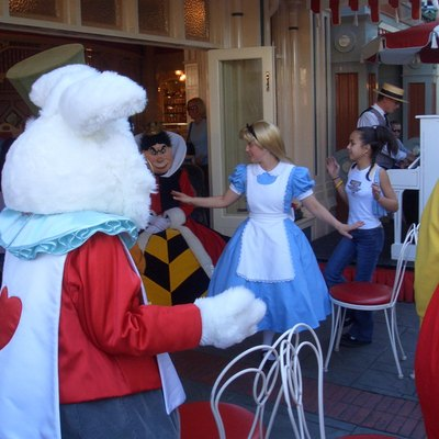 A Disneyland actress costumed as the title character of the 1951 film Alice in Wonderland is shown playing musical chairs with actors representing other characters from that film at Coca-Cola Refreshment Corner on Main Street (also known simply as