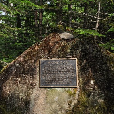 This marker stands on the Appalachian Trail between Mounts Spaulding and Sugarloaf in Maine, in commemoration of the trail's completion by a CCC crew in 1937. It reads