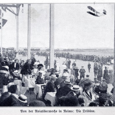 Photograph (taken from a catholic german magazin from 1910) of a biplane flying past the tribune of the Aviation week in Reims, France, August 22 - 29, 1909.