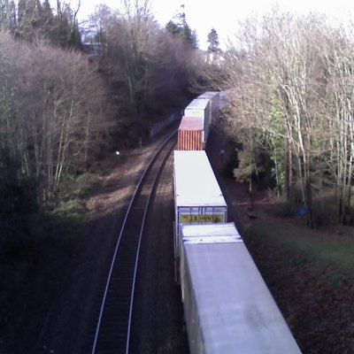Photograph facing west, taken from the pedestrian bridge over the BNSF Railway tracks in Magnolia, Seattle, just south of Commodore Park. Kiwanis Ravine is to the left.