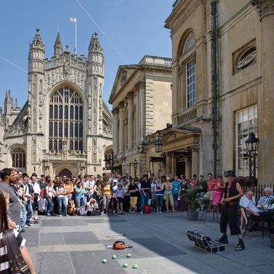 Bath Abbey and Entertainer. Bath is very popular with tourists, particularly in the summer, and the city bustles with life. An entertainer performs for the crowd in front of the Bath Abbey and to the right, the Roman Baths. Taken by myself with a Canon 5D and 24-105mm f/4L IS lens.