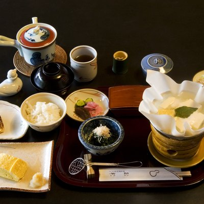 A Traditional breakfast at Tamahan Ryokan, Kyoto. The dishes include roast mackerel, dashimaki (Japanese omelette, here Kansai style), rice, a paper pot (kami nabe) of yudofu over a small brasier, with soy sauce and toppings (negi and katsuobushi), tsukemono (cucumber, pickling melon, turnip) and green tea. In the black cup is miso soup.