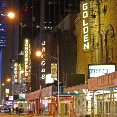 Nighttime photo of the Broadway theaters on West 45th Street (George Abbott Way) in New York City. From right to left, the Golden Theater showing Oleanna; the Jacobs Theater showing God of Carnage; the Schoenfeld Theatre showing A Steady Rain, and the Booth Theater, showing Next to Normal.