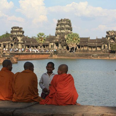 Buddhist monks enjoying afternoon breeze in front of moat of Angkor Wat, Siem Reap, Cambodia.