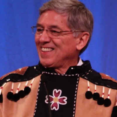 New Alaska Lt. Gov. Byron Mallott smiles after telling a joke during his inauguration speech Monday, Dec. 1, 2014 in Juneau, Alaska's Centennial Hall. Mallott, a Tlingit Alaska Native from Yakutat, wore traditional regalia during the ceremony. Cropped from original.