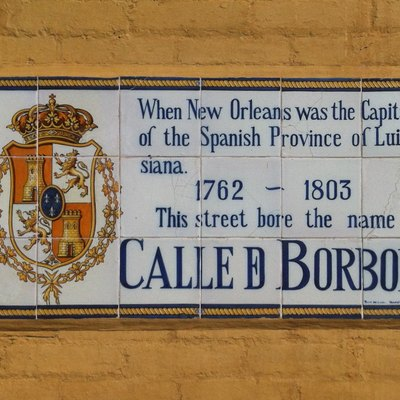 Mosaic tile plaque on an exterior building wall on Bourbon Street in New Orleans. The text explains the origin of the name Bourbon Street. It reads