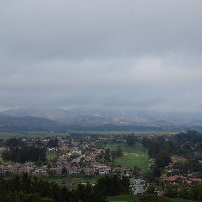 A view of Camarillo, California from Spanish Hills Country Club on a cloudy April day. A residential community is in the foreground, while mountains and gray clouds lie in the background.