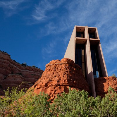 A picture of the Chapel of the Holy Cross in Sedona, Arizona near sunset. The chapel appears to rise out of the rock formations characteristic of the area.