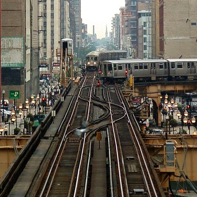 A Brown line train and Orange line train contend for the intersection at the southeast corner of the Loop in Chicago. Photograph taken from the crossover walkway of the Adams/Wabash stop on the Green, Orange, Brown, and Purple lines.