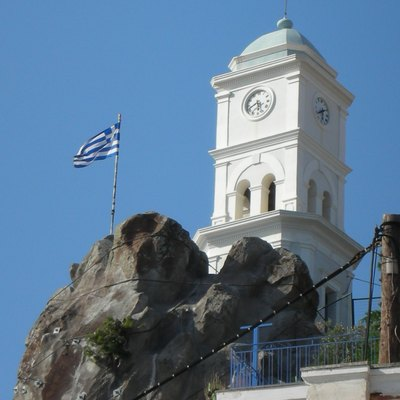 Clock tower, Poros Island, the Saronic Gulf Islands (Gulf of Aegina), Greece. The picturesque town of Poros with its beautiful neoclassical buildings is built amphitheatrically on the slopes of a hill. Its most famous landmark is a clock tower, built in 1927.