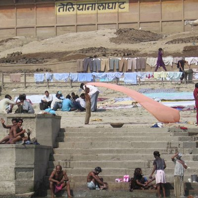 People drying clothes, getting dressed or washing by the steps down to a river (Ganges?) in India.