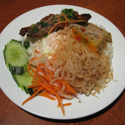Vietnamese broken rice (cơm tấm) with grilled pork, shredded pork and pork skin, fried egg, pork meat loaf, picked carrot and sliced cucumber from Ha Long Bay restaurant in Richmond, Victoria, Australia.