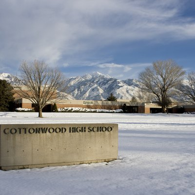 Cottonwood High School in Murray, Utah. The photo shows the Cottonwood High sign in the foreground with the school in the background, against a backdrop of the Wasatch Mountains. Taken from the north-west corner of the campus.
