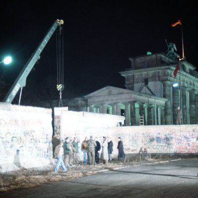 East and West Germans converge at the newly created opening in the Berlin Wall after a crane removed a section of the structure beside the Brandenburg Gate.